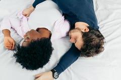 Молодые пары спать совместно на кровати в спальне, обнимая один другого сладко стоковое фото