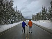 Молодые пары стоя на дороге держа руки Новобрачные около Revelstok взгляд vancouver воздушной Британского Колумбии городской Кана Стоковая Фотография
