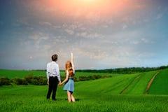 Молодые пары стоя на зеленом поле, женщине показывая ее руку на стоковая фотография rf