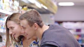 Молодые пары с покупками тележки в супермаркете сток-видео