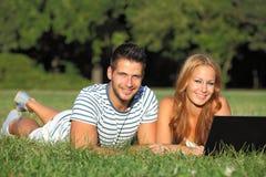 Молодые пары с тетрадью в парке Стоковая Фотография RF