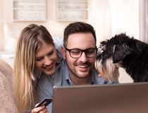 Молодые пары с ходить по магазинам собаки онлайн дома Стоковое Фото