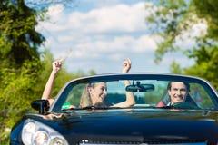 Молодые пары с cabriolet в лете на день задействуют Стоковые Изображения RF