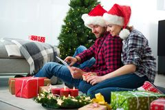 Молодые пары с gif рождества шляп Санта Клауса ходя по магазинам онлайн Стоковое фото RF