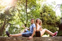 Молодые пары с smartphones в городке сидя на бетонной стене Стоковое Изображение RF