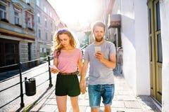 Молодые пары с smartphones на улице Стоковые Фото