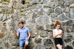 Молодые пары с smartphones против каменной стены в городке Стоковое Изображение RF