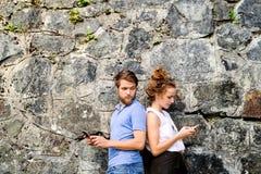 Молодые пары с smartphones против каменной стены в городке Стоковая Фотография RF