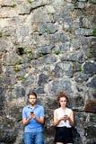 Молодые пары с smartphones против каменной стены в городке Стоковое Изображение