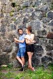 Молодые пары с smartphones против каменной стены в городке Стоковые Фото