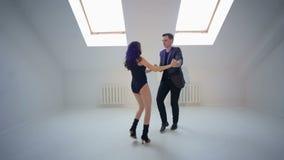 Молодые пары танцуя bachata на танцевальном зале сток-видео