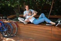 Молодые пары тратя время совместно в парке с велосипедами близрасположенными Мальчик сидя на стенде в парке с милой девушкой с Стоковая Фотография