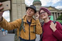Молодые пары туристов принимая selfies против собора Казани в Санкт-Петербурге, России стоковое изображение