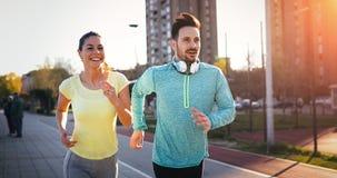 Молодые пары фитнеса бежать в городской местности стоковые фотографии rf