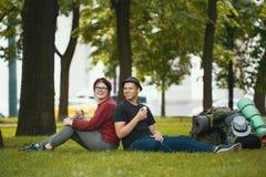 Молодые пары - человек и женщина - туристы с рюкзаками едят мороженое в парке Стоковая Фотография