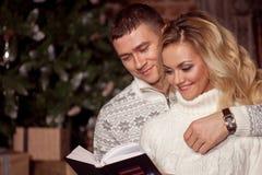 Молодые пары читая книгу совместно на предпосылке рождественской елки Стоковое Изображение RF