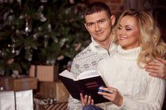 Молодые пары читая книгу совместно на предпосылке рождественской елки Стоковые Фото
