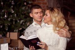 Молодые пары читая книгу совместно на предпосылке рождественской елки Стоковое фото RF
