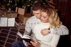Молодые пары читая книгу совместно Стоковые Изображения RF