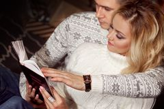 Молодые пары читая книгу совместно Стоковое Фото