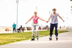 Молодые пары rollerblading в парке держа руки Стоковое Изображение