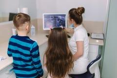 Молодые пациенты девушка и взгляд мальчика на снимке рентгеновского снимка монитора стоковые изображения rf