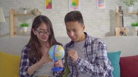Молодые положительные пары sian с глобусом в их руках видеоматериал
