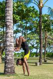 Молодые практикующий врачи человека йоги делая йогу на природе Азиатский индийский человек yogis на траве в парке Остров Бали Стоковая Фотография