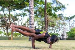 Молодые практикующий врачи человека йоги делая йогу на природе Азиатский индийский человек yogis на траве в парке Остров Бали Стоковое фото RF