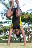 Молодые практикующий врачи человека йоги делая йогу на природе Азиатский индийский человек yogis на траве в парке Остров Бали Стоковые Фото