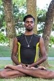 Молодые практикующий врачи человека йоги делая йогу на природе Азиатский индийский человек yogis на траве в парке Остров Бали Стоковая Фотография RF
