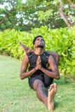 Молодые практикующий врачи человека йоги делая йогу на природе Азиатский индийский человек yogis на траве в парке Остров Бали Стоковое Фото