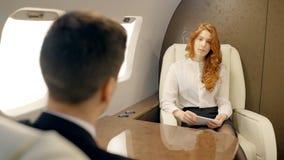 Молодые предприниматели обсуждают проект сидя на таблице в интерьере самолета сток-видео
