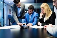 Молодые предприниматели работая на компьютере в офисе стоковая фотография