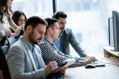 Молодые предприниматели работая на компьютере в офисе Стоковое Изображение RF