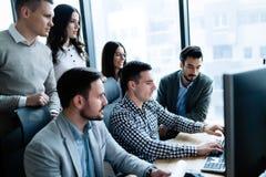 Молодые предприниматели работая на компьютере в офисе стоковое изображение