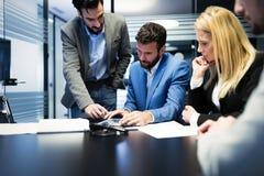 Молодые предприниматели работая на компьютере в офисе Стоковые Фото