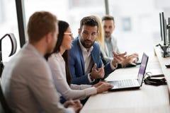 Молодые предприниматели работая на компьютере в офисе Стоковое фото RF
