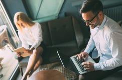 Молодые предприниматели работая на компьютере в офисе стоковые изображения