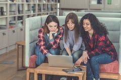 Молодые привлекательные девушки с компьтер-книжкой Стоковое фото RF
