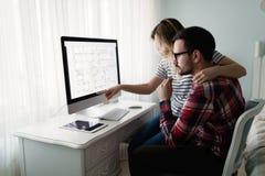 Молодые привлекательные дизайнеры работая совместно от дома Стоковые Изображения RF