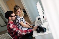Молодые привлекательные дизайнеры работая совместно от дома Стоковые Фотографии RF