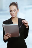 Молодые привлекательные документы подряда чтения женщины дела Стоковая Фотография