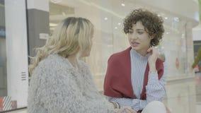 Молодые привлекательные женские друзья встречая в моле после долгого времени сидя на стенде и говоря о покупках - сток-видео
