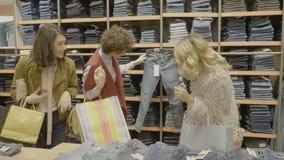 Молодые привлекательные женские модели имея потеху пока ходящ по магазинам и смотрящ пару джинсов для того чтобы ходить по магази акции видеоматериалы