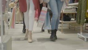 Молодые привлекательные женские покупатели смотря одежды в магазине мола и идя медленно к камере - сток-видео