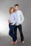 Молодые привлекательные женщина и человек над серым цветом Стоковые Изображения RF