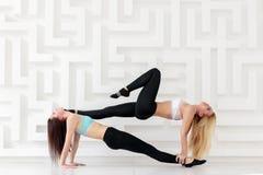 Молодые привлекательные женщины практикуя представление йоги acro баланса стоковое фото