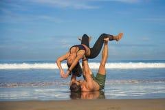 Молодые привлекательные и сконцентрированные пары акробатов практикуя баланс йоги acro и тренировку раздумья на красивом пляже вн стоковая фотография
