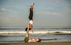 Молодые привлекательные и сконцентрированные пары акробатов практикуя баланс йоги acro и тренировку раздумья на красивом пляже вн стоковое фото